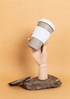 Drewniany manekin ręka trzyma kubek kawy wielokrotnego użytku