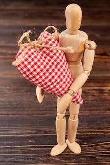 Drewniany manekin trzyma czerwone serce w kratkę. drewniana figura z ręcznie robionym sercem stojącym na brązowym tle drewnianych. prezent na walentynki.