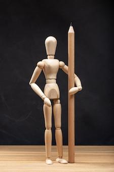 Drewniany manekin trzyma ołówek. koncepcja rysowania lub projektowania