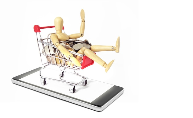 Drewniany manekin ze srebrną monetą w koszyku na telefonie komórkowym na białym tle. koncepcja zakupy online.