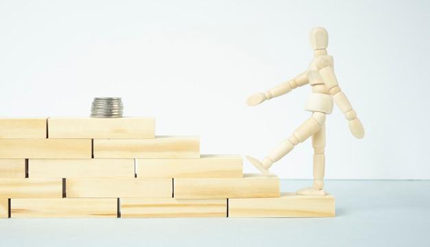 Drewniany mężczyzna idący po schodach, aby dostać się do stosu monet na białym tle
