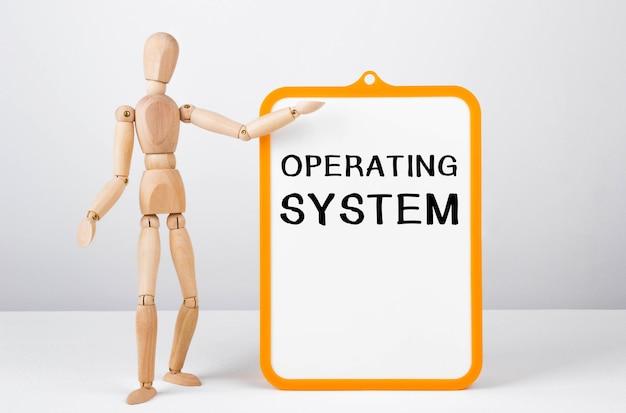 Drewniany mężczyzna pokazuje ręką białą tablicę z napisem system operacyjny.