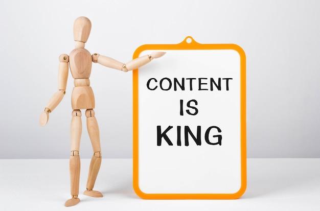 Drewniany mężczyzna pokazuje ręką białą tablicę z tekstem content is king, concept