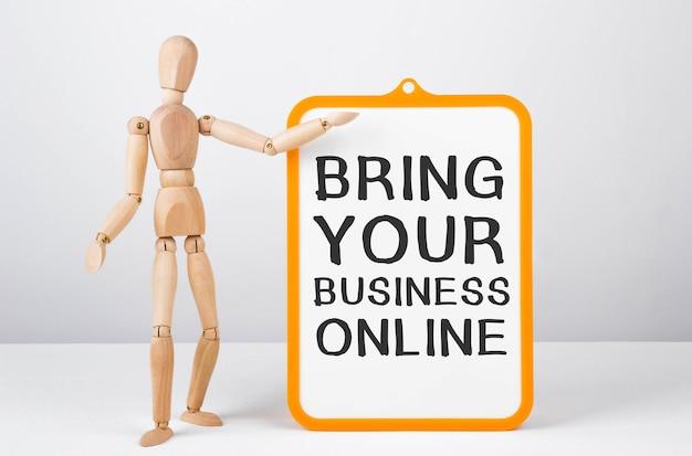 Drewniany mężczyzna pokazuje ręką białą tablicę z tekstem przenieś swoją firmę do internetu.