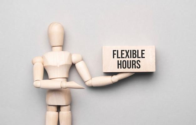 Drewniany mężczyzna pokazuje z ręką do białej tablicy z tekstem godziny elastyczne, koncepcja