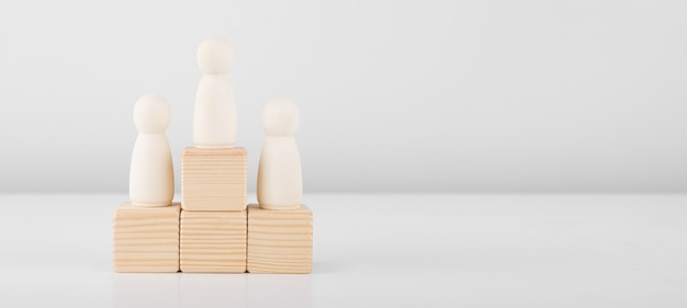 Drewniany mężczyzna reprezentujący lidera zwiększa sukcesy, stojąc na piedestale.