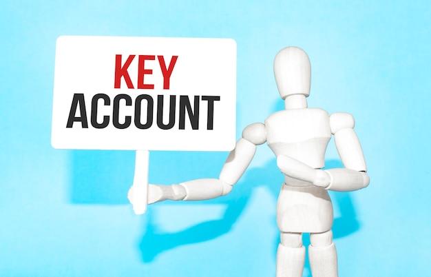 Drewniany mężczyzna trzyma w rękach biały znak z napisem konto kluczowe. treść napisu ma wpływ na koncepcję biznesową i marketing.
