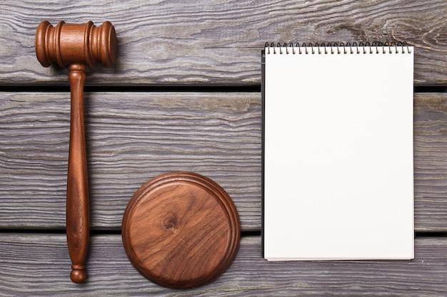Drewniany młotek i czysty notes. widok z góry młotek sędziego i pusty notatnik na drewnianym stole.