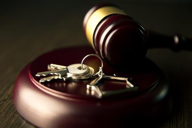 Drewniany młotek i dom do kupna lub sprzedaży domu, licytacji lub prawnika nieruchomości i koncepcji budynku.