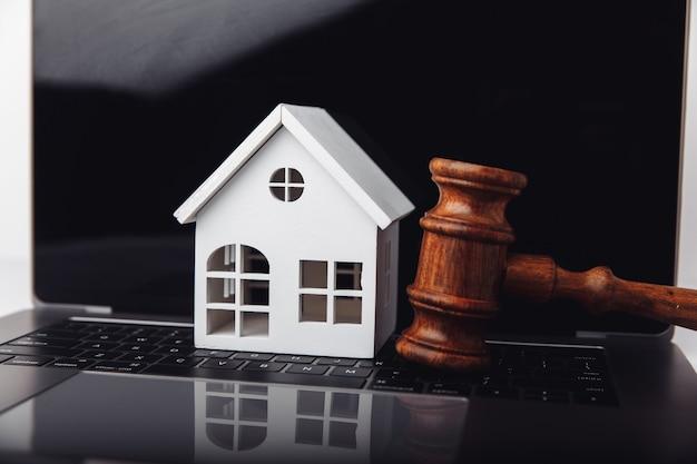 Drewniany młotek i dom na aukcji internetowej laptopa