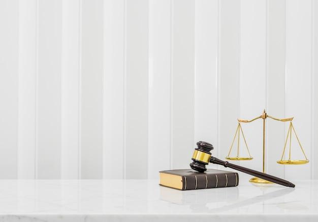 Drewniany młotek i książka prawa postawione na białym marmurowym blacie stołu