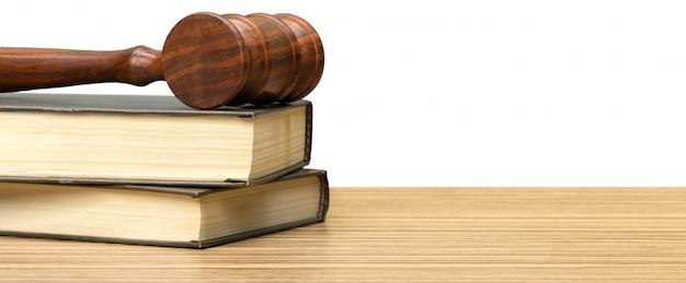 Drewniany młotek i książki na drewnianym stole
