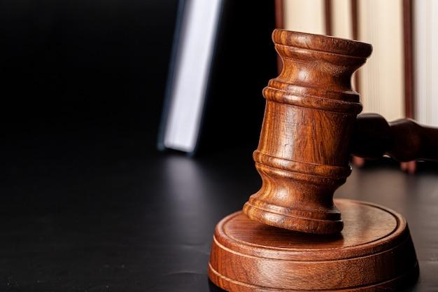 Drewniany młotek i książki prawnicze z bliska