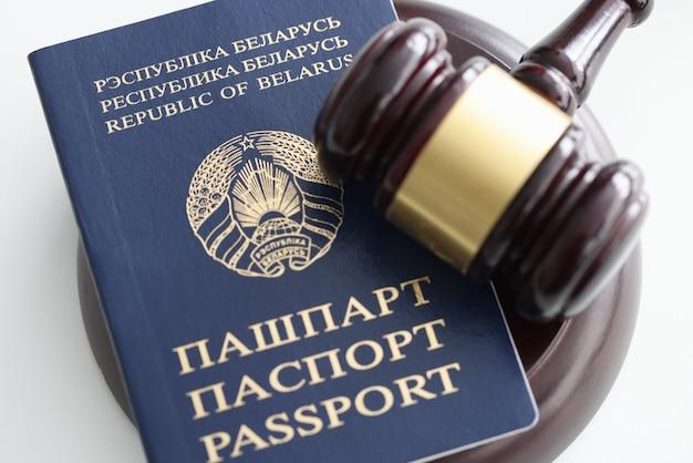 Drewniany młotek i paszport sędziego. emigracja do innego pojęcia kraju