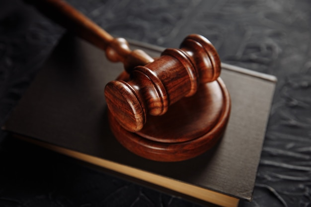 Drewniany młotek i prawnicza książka na stole.