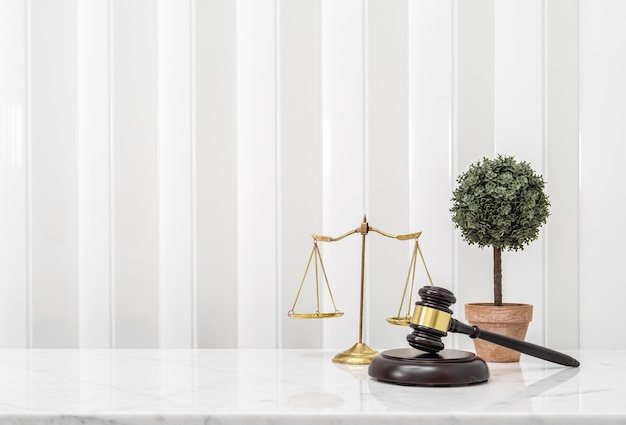 Drewniany młotek i wagi równowagi adwokata na białym blacie marmurowym blatem
