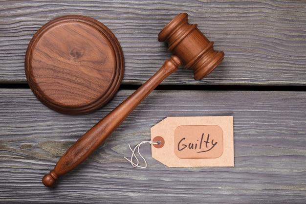 Drewniany młotek i wyrok winy. młotek brązowy widok z góry. pojęcie sądu i prawa.