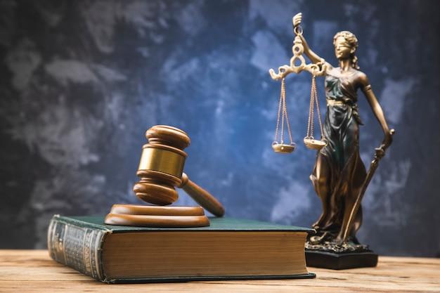 Drewniany młotek na księdze prawniczej i pani sprawiedliwości