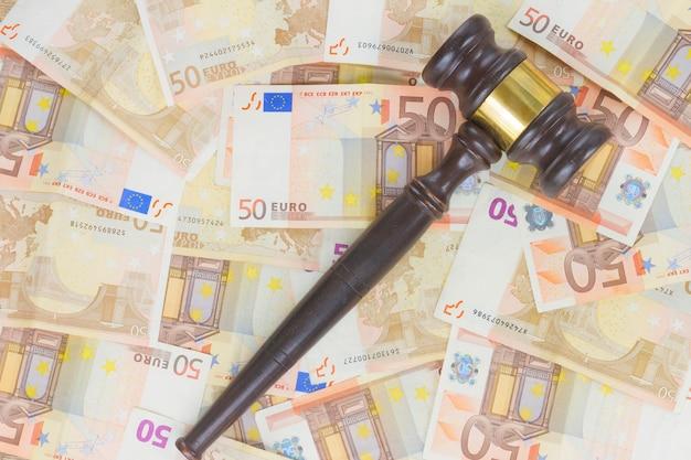 Drewniany młotek prawniczy i tło banknotów euro
