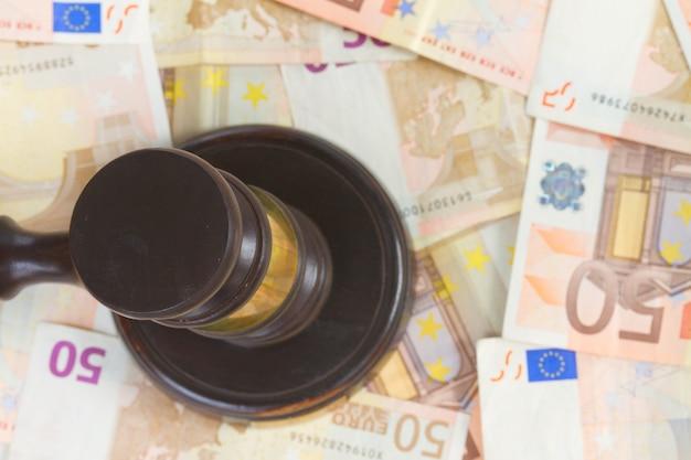 Drewniany młotek prawniczy na tle pieniędzy euro, widok z góry