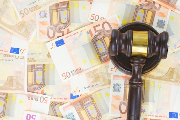 Drewniany młotek prawniczy na tle pieniędzy euro