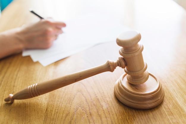 Drewniany młotek przed sędzią piszącym na dokumencie