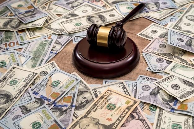 Drewniany młotek sędzia na tle dolarów