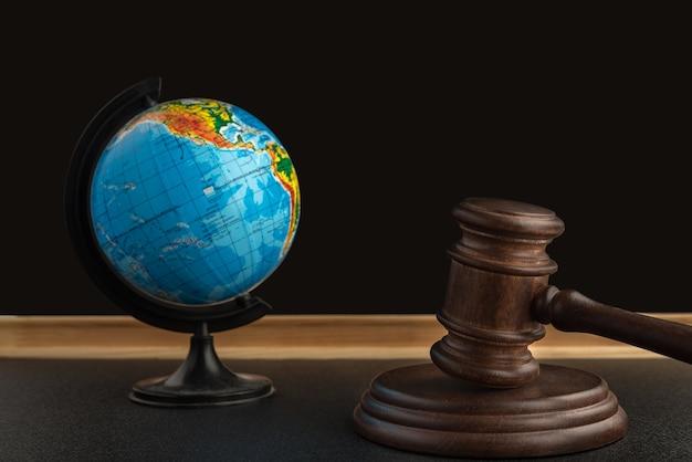 Drewniany młotek sędziego i kula ziemska.