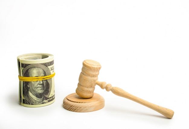 Drewniany młotek sędziego i pakiet dolarów na białym tle.