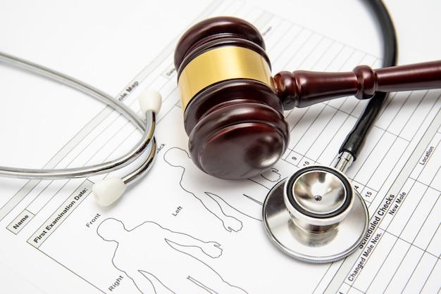 Drewniany młotek sędziego i stetoskop na karcie medycznej.
