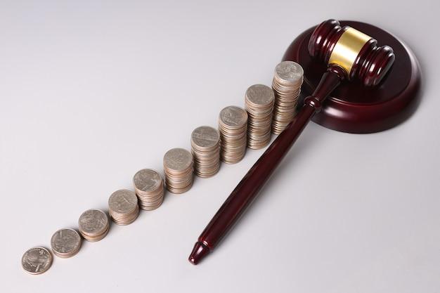 Drewniany młotek sędziego i stosy monet na stole. przestępstwa kryminalne w koncepcji sfery gospodarczej