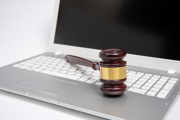 Drewniany młotek sędziego na srebrnym komputerze przenośnym