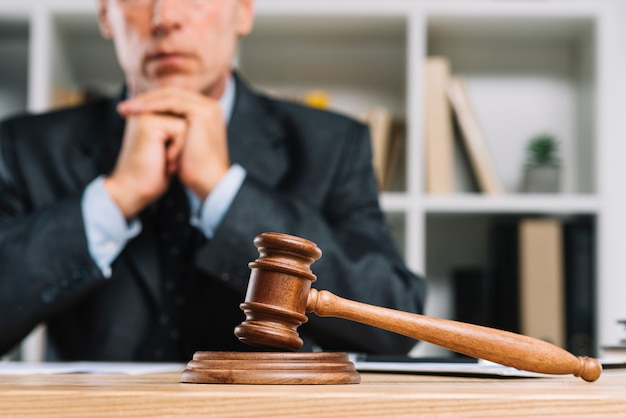 Drewniany młotek sędziego na stole przed prawnikiem