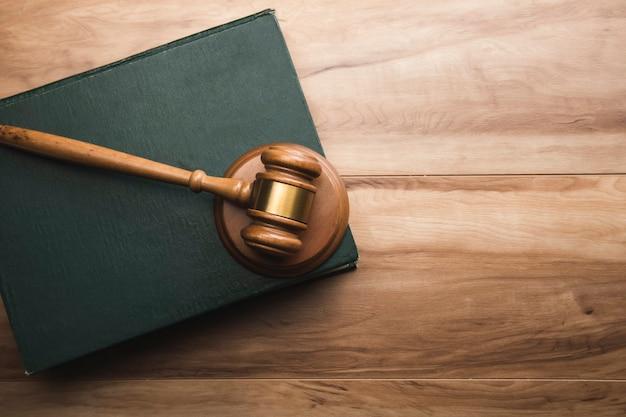 Drewniany młotek sędziowski i prawna książka na drewnianym stole