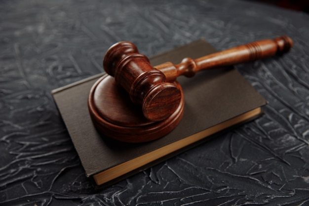 Drewniany młotek sędziowski leżący na księdze prawniczej na sali sądowej w celu wymierzenia sprawiedliwości i skazywania przestępstw.