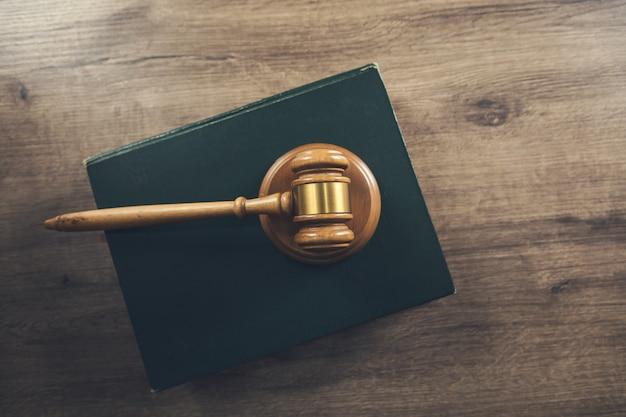 Drewniany młotek sędziowski leżący na księdze prawniczej