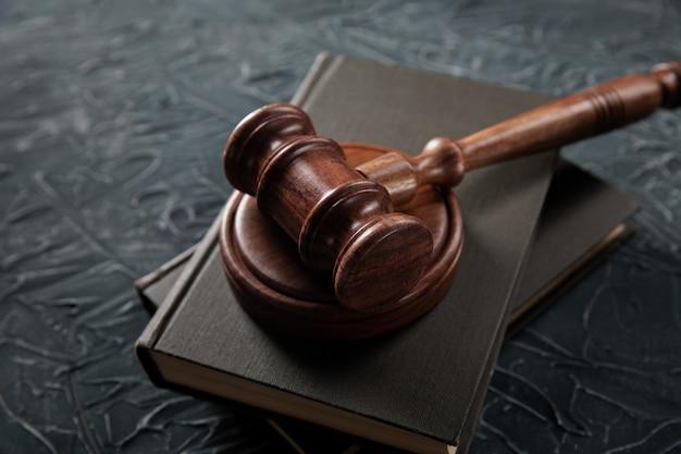 Drewniany młotek sędziowski leżący na księgach prawniczych na sali sądowej w celu wymierzenia sprawiedliwości i skazywania przestępstw.