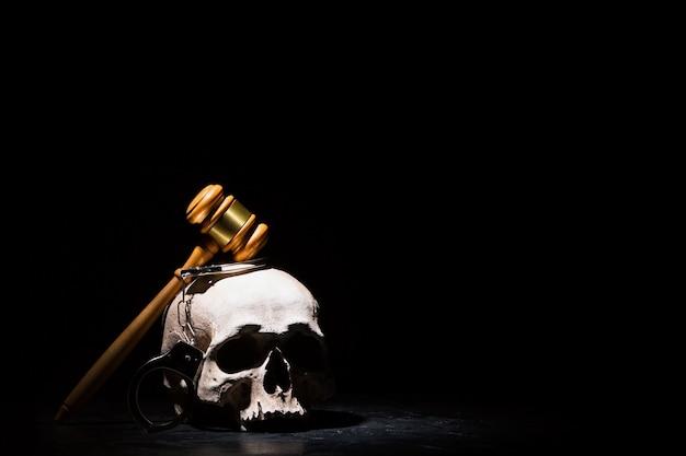 Drewniany młotek sędziowski na ludzkiej czaszce z kajdankami