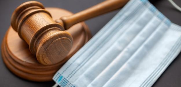 Drewniany młotek sędziowski z maską medyczną. prawodawstwo dotyczące opieki zdrowotnej i pojęcie medyczne