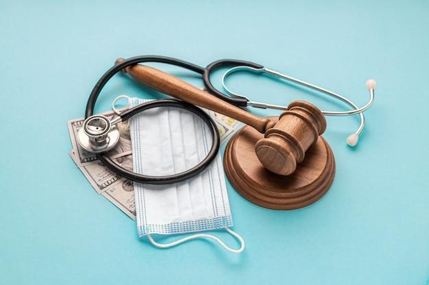 Drewniany młotek sędziowski z maską medyczną, stetoskopem lekarskim i pieniędzmi na niebieskim tle. prawodawstwo dotyczące opieki zdrowotnej i pojęcie medyczne