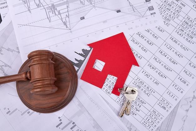 Drewniany młotek z domkiem i kluczami na dokumentach