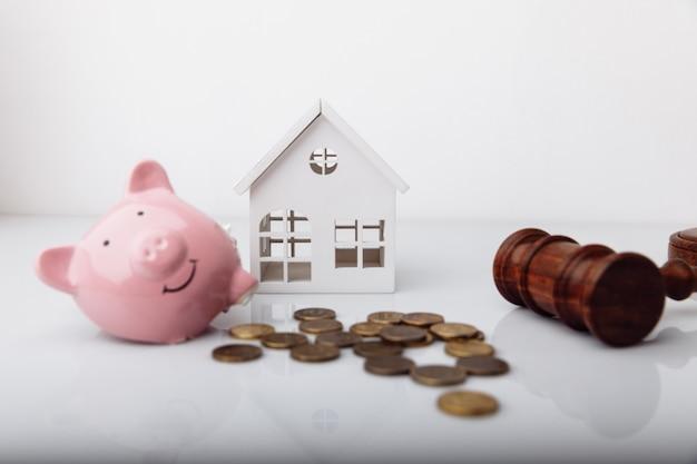 Drewniany młotek zepsuty skarbonka i model domu z aukcją monet i koncepcją upadłości