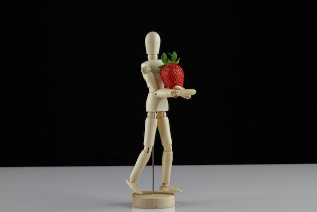 Drewniany model człowieka i czerwona truskawka