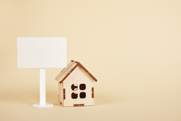 Drewniany model domu i biały pusty znak na beżowym tle miejsce na kopię pojęcie nieruchomości