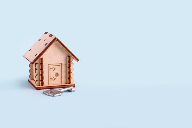 Drewniany model domu i klucz na niebieskim tle. koncepcja kupna i sprzedaży domów i nieruchomości. ubezpieczenie domu, nieruchomości i hipoteka. skopiuj miejsce na tekst