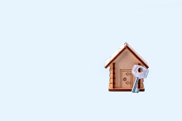 Drewniany model domu i klucz na niebieskim tle. koncepcja kupna i sprzedaży domów i nieruchomości. ubezpieczenie domu, nieruchomości i hipoteka. skopiuj miejsce na tekst.