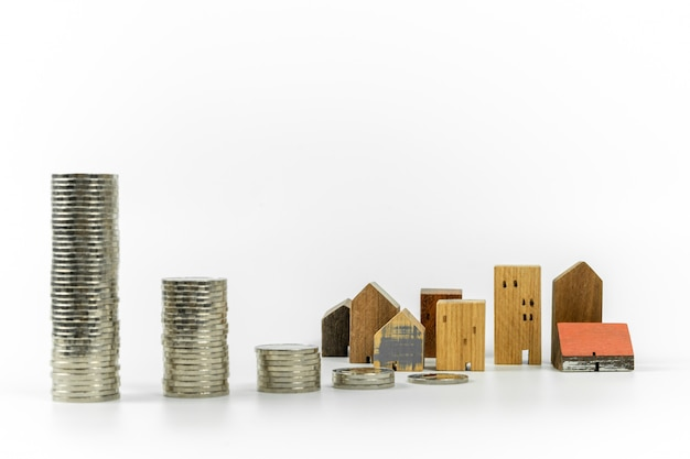 Drewniany model domu i rząd monety na białym tle, izolować,