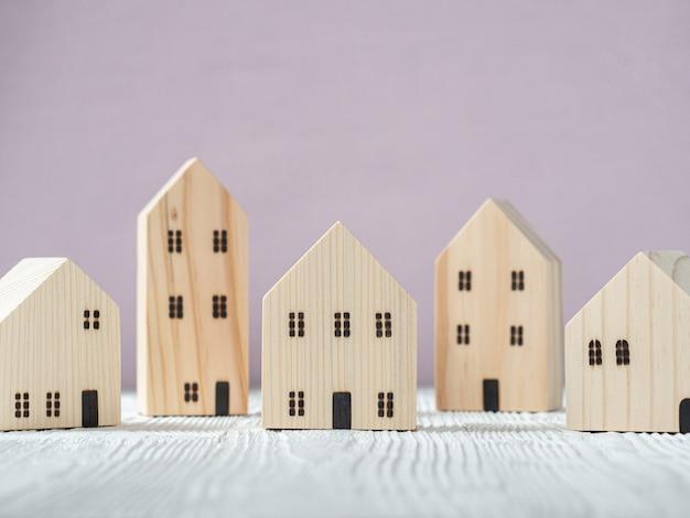 Drewniany model domu na białym tle drewna i różowym. plan hipoteczny dla branży mieszkaniowej i strategia oszczędzania na podatku od nieruchomości