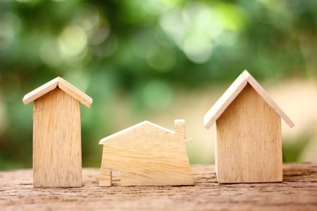 Drewniany model domu na drewnianej podłodze w stylu retro z zielonym tłem rozmycia
