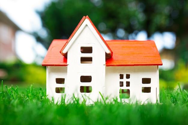 Drewniany model domu na trawie, lato na zewnątrz, nowa koncepcja domu